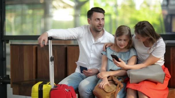 Matka a otec s roztomilou dcerou sedí v čekárně na nádraží nebo na letišti. Hezká Máma ukazuje telefon. Děti se hledají v telefonu Smartphone.