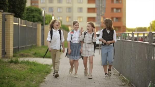 Gyermekek hátizsákok megy a parkban közelében iskola. Két fiú és két lány hazatért az iskola után. Vissza az iskolába