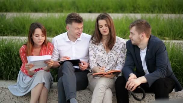 Skupina čtyř studentů sedících v parku a mluvení k sobě navzájem. Čtou sešity, relaxují, mluví venku v univerzitním táboře.