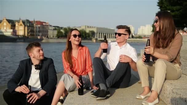 Un gruppo di studenti che si divertono allaperto. Bevono birra, parlano tra loro e ridono. Il tempo estivo sembra grande sullo sfondo.
