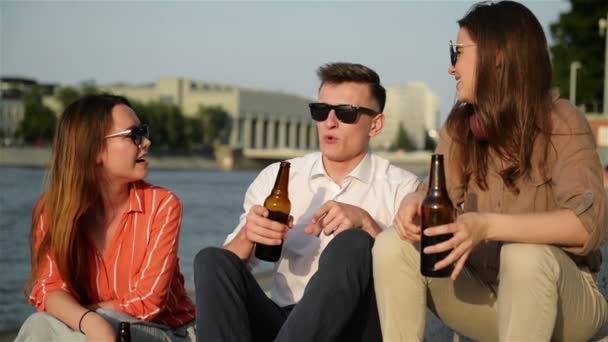 A Group Of Students Having Fun Outdoors. They Are Drinking Beer, Talking To Each Other And Laughing. Summertime Weather Looks Great On Background.