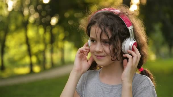 Girl Lying On The Grass And Listening To Music On Headphones. Cute Little Caucasian Kid Is Having Fun Chilling Out Outdoors.