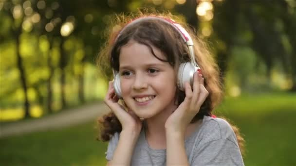 Portrait of Beautiful Caucasian Little Girl Spending Time In Public Park. Student Kid Having a Lot of Fun Relaxing Outdoors and Listening To Music With Headphones.