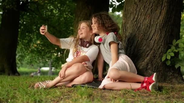 Childhood Time. Cute Smiling Little Girls Enjoying in the Park While Making a Selfie And Listening To Music With Mobile Phone.