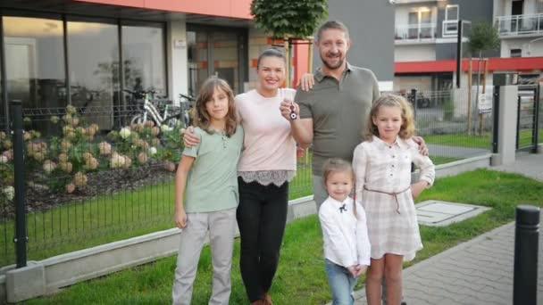 Familie mit Kindern schaut in die Kamera, die draußen auf der Straße steht. Paar und Kinder kaufen ein neues Zuhause. Immobilienbesitzer mit Schlüsseln umarmen sich und posieren mit Sohn und Tochter. Hypothekendarlehen.