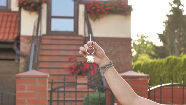 Halten Sie Keys auf House Closeup vor einem neuen Haus. Konzept der Immobilien