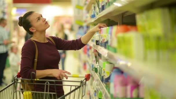 Mladé ženy zvolí ubrousky ze supermarketu police. Dívka s Kavkazský vzhled uskuteční nákup v supermarketu. HD, vozík, položky, Supermarket interiér.