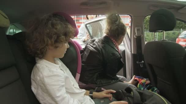 Gyönyörű felnőtt anya kinyitja a kocsiajtót tinédzser lányának és fiának, búcsúcsókot ad nekik, mielőtt reggel leckéket vennének. Gondoskodó anya, aki elviszi a gyerekeket az iskolába..