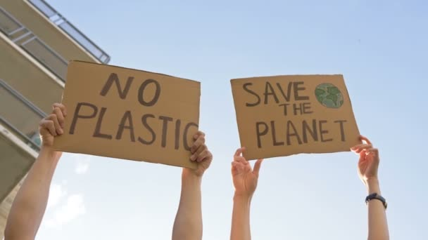 Female hands holding posters SAVE THE PLANET and NO PLASTIC.