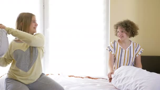 Two teen pyjamas girls having pillow fight on bed. They are laughing to each other.