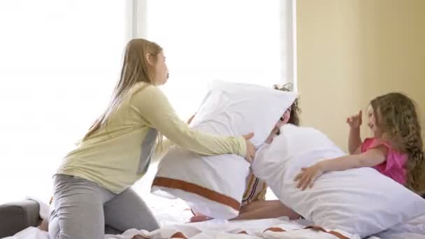 Three girls of school age arranged a comic pillow battle in the bedroom. Favorite childrens game.