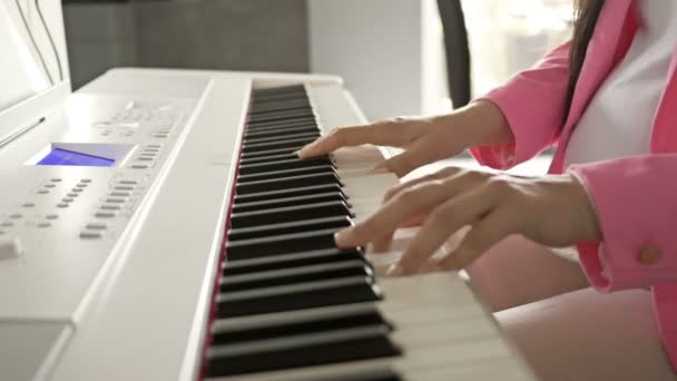 Pregnant young woman plays on a white digital piano for the baby.