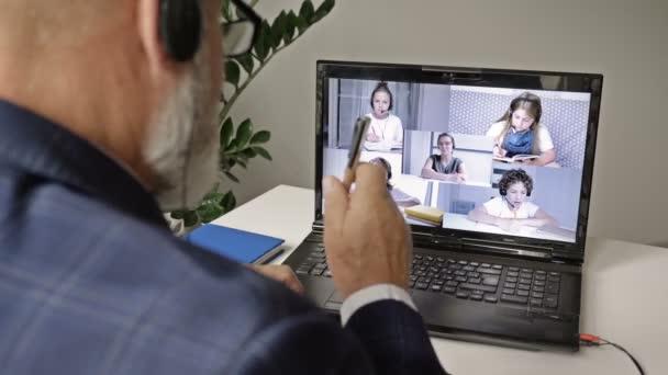 Ein erfahrener Oberlehrer nutzt einen Laptop, um eine Online-Lektion zu beobachten und einem jungen Lehrer Ratschläge zu erteilen.