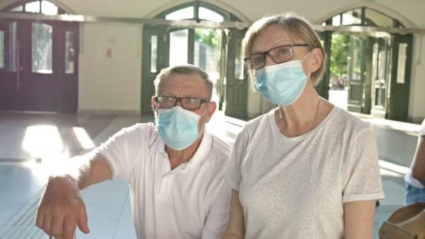 Egy idős pár várja a gépét a váróban. Orvosi maszkok vannak az arcukon. Utazás, turizmus a koronavírus járvány idején.