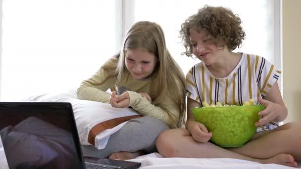 Egy portré boldog tinédzser lányokról, akik komédiát néznek az ágyban és nevetnek. Vidám barátok eszik ízletes popcorn és keres film örömmel.