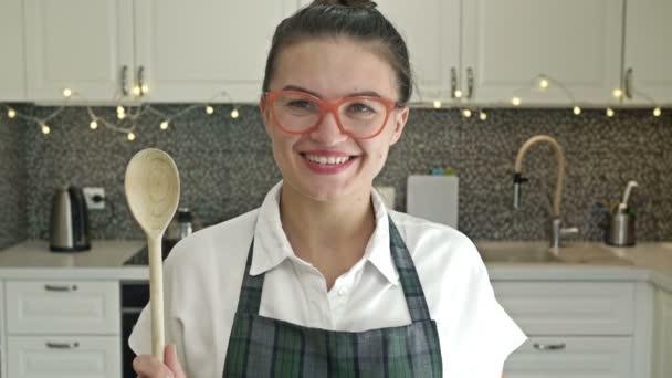 Portrét veselé mladé ženy v zástěře s dřevěnou lžící v ruce na pozadí kuchyňského nábytku.