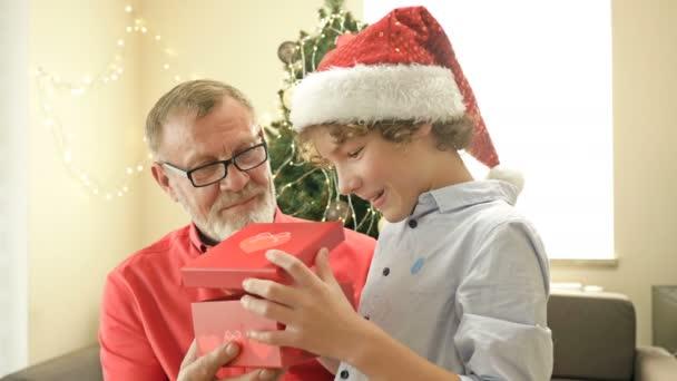 Opa mit Nikolausmütze macht seinem Teenager-Enkel ein Weihnachtsgeschenk. Der Junge freut sich über das Geschenk. Vor dem Hintergrund des Weihnachtsbaums. Frohe Weihnachten. Frohes neues Jahr.