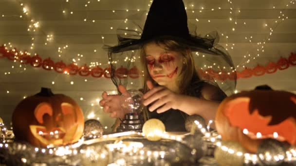 Teenage dívka oblečená jako čarodějnice s děsivým make-upem na tváři. Dívka vykouzlí nad kouzelnou koulí. Tmavě zlaté pozadí. Halloween.