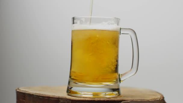 Pivo se nalévá do sklenice na pivo s rukojetí, spoustou bublin a pěny, která stéká po skle.