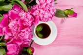 Fotografie Bouquet Peony flowers on pink backgroun and  cup of coffee. Copy space.  flat lay. Good morning.