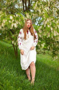 """Картина, постер, плакат, фотообои """"Украинская девушка в длинные рубашка с вышивкой, соблазнительно позирует против белая акация цветет"""", артикул 205950098"""