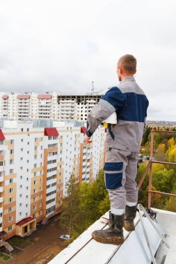 the builder looks at the constructed buildings from the roof