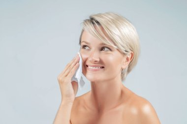 Beautiful woman is removing makeup from her face with oil tissue. Beauty and clean face