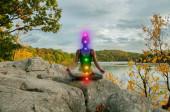 Žena medituje s zářící sedmi Chakry na kamenné terase. Žena cvičila jómu na jezeře.