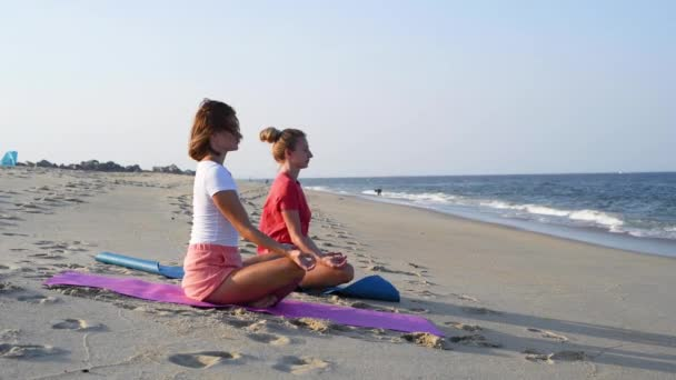 Young women practicing yoga on calm beach at sunset. Girls meditating, sitting in lotus pose on the sea shore.