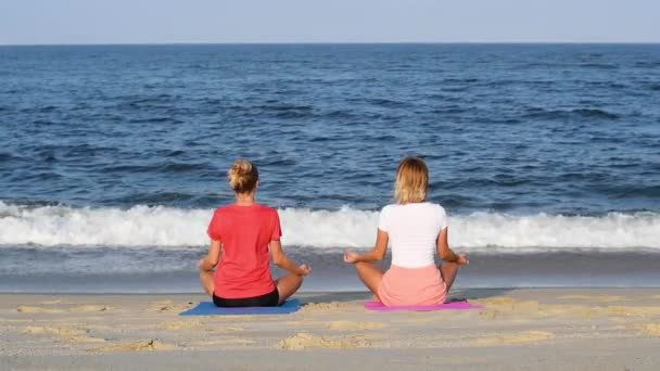 Young women practicing yoga on calm beach at sunset. Girls meditating, sitting in lotus pose on the sea shore. Slow motion