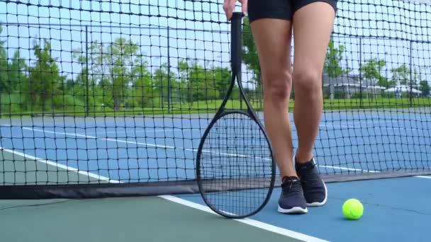 Žena s tenisovou raketou. Ženské nohy s tenisovou raketou