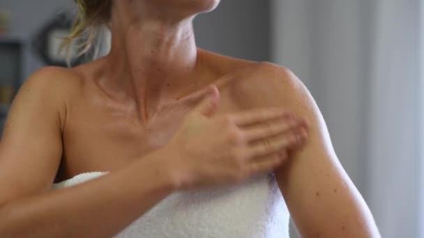 cura della pelle. Bella donna avvolta in asciugamano dopo la doccia sta diffondendo lozione per il corpo sulla pelle abbronzata