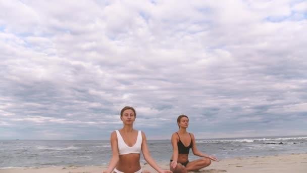 Fiatal nők gyakorló jóga a strandon lassított. Lányok meditál, ül lótusz pózol a tenger parton.