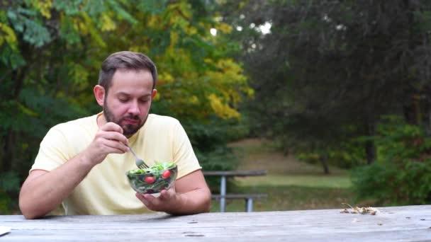 Ember eszik friss salátával ül a parkban. Egészséges táplálkozás, diétás koncepció és vegetáriánus ételek