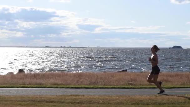 Attraente giovane donna in esecuzione atleta resistenza corridore di allenamento jogging cardio esercizio fisico sulla tranquilla spiaggia oceanica in movimento lento