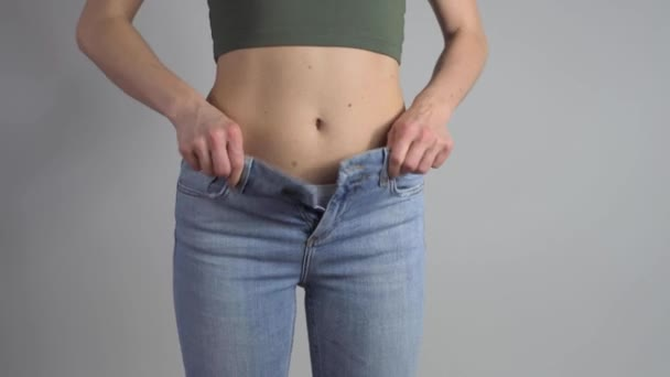 Slim woman is putting on a pair of jeans and knotoning zip fastener then shows perfect pas after successful lost weight. Na šedém pozadí
