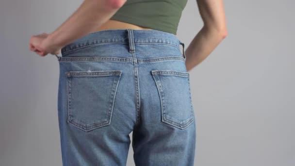 A túlméretezett farmeres vékony nő tökéletes derekat mutat a fogyás után..
