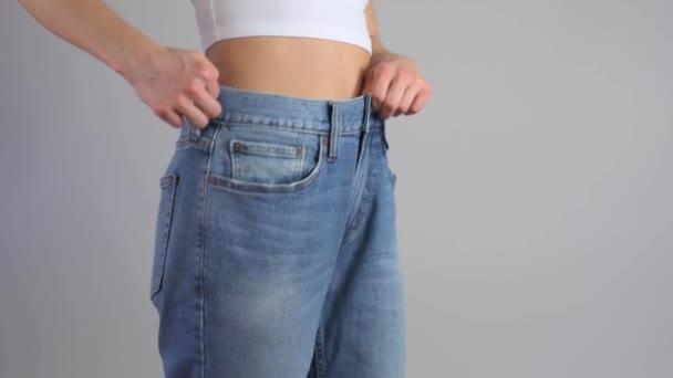 Hubená žena v nadrozměrných džínách ukazuje perfektní pas po zhubnutí.
