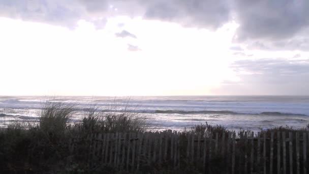 Vlny na pobřeží Atlantského oceánu během zamlžené západ slunce