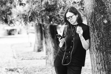 Young woman blogger drink coffee during summer walk with modern device. Cute girl enjoying favorite playlist via earphones. Blogger girl checking her smartphone while drinking a coffee outdoors