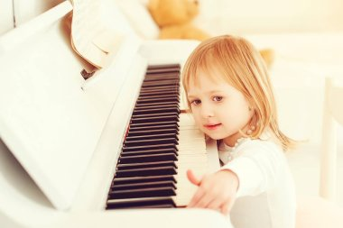 Cute little girl playing piano at a music school. Preschool child learning to play music instrument. Education, skills concept. Little princess is happy playing the piano. Happy childhood