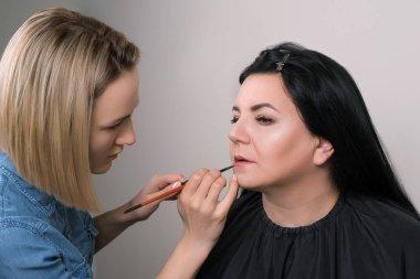 Makeup artist applies lipstick. Beautiful mature woman at beauty salon. Makeup artist doing makeup for charming woman. Happy senior woman with professional make-up artist at studio