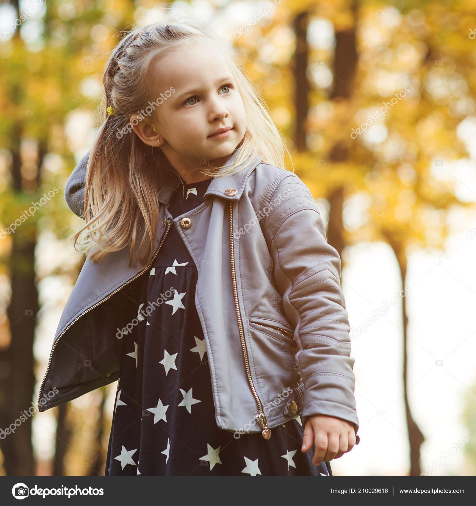 d40a664f200 Ευτυχισμένη παιδική ηλικία. Κομψό κορίτσι παίζει στο πάρκο της πόλης. Φθινοπωρινή  μόδα για τα παιδιά. Εποχιακές πωλήσεις — Εικόνα από Volurol