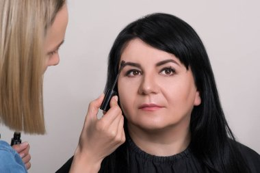 Eyebrow care. Beautiful mature woman at beauty salon. Makeup artist doing nude makeup for charming woman. Happy senior woman with professional make-up artist at studio