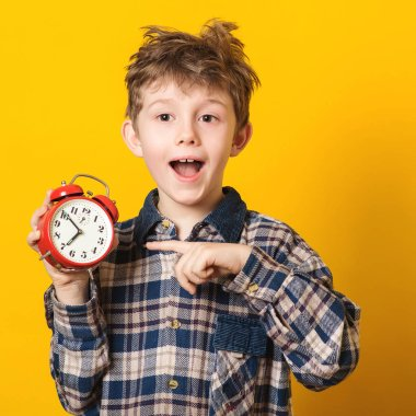 Cute little boy with alarm clock,isolated on yellow. Funny kid pointing at alarm clock at 7 o'clock at morning. Excited boy overslept before school. People, school, time and lifestyle concept