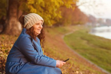 Young attractive girl using smartphone outdoors. Happy hipster girl walking in autumn day. Beautiful girl listen music on autumn walk. Woman wear autumn clothes and enjoying autumn sunny weather