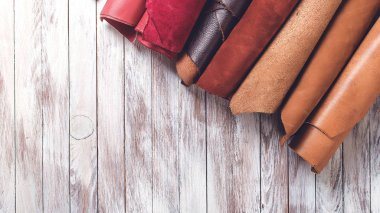 Multi colored leather in rolls. Flat lay. Rolls of natural color leather. Materials for leather craft. Copy space. Top view. Handmade craft. Different samples of leather on wooden table