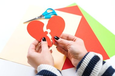 Red heart puzzle. Woman hands holds two part of paper heart. Happy Valentine's day. Concept of love