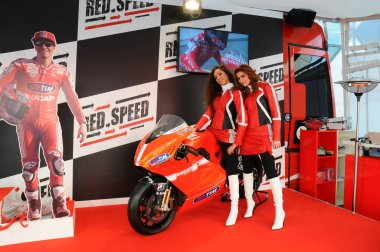 BOLOGNA, ITALY - DECEMBER 2, 2010: beautiful young models poses on DUCATI Motorbike at the Bologna Motor Show. Italy