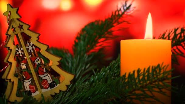Brennende Kerze mit Weihnachtsschmuck aus grünen Tannenzweigen und Bokeh aus Lichtern. Weihnachtsstimmung. 4K-UHD-Video.